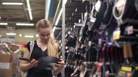 La femme de sourire regarde sur une nouvelle poêle dans un magasin de matériel banque de vidéos