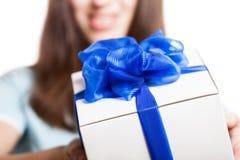La femme de sourire remettent tenir le cadeau ou la boîte actuelle Photographie stock libre de droits
