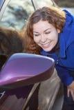 La femme s'admirent dans le miroir latéral rétroviseur de voiture Image stock