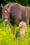 La femme de sourire s'assied dans le pré avec son cheval Arabe Images libres de droits
