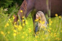 La femme de sourire s'assied dans le pré avec son cheval Arabe Photographie stock libre de droits