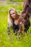 La femme de sourire s'assied dans le pré avec son cheval Arabe Image stock