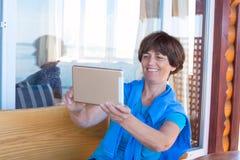 La femme de sourire s'assied sur la véranda utilisant le comprimé Images stock