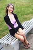 La femme de sourire s'assied sur un banc Images stock