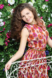 La femme de sourire se tient dessus de retour du banc blanc Image stock