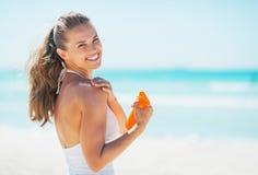 La femme de sourire sur la plage appliquant le soleil bloquent la crème Photo libre de droits