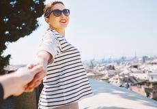 La femme de sourire tire pour la main son ami sur le point de vue supérieure sur la ville Photo libre de droits