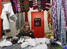 La femme de sourire vend les vêtements chauds sur le marché de Noël de Riga Image stock