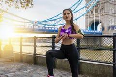 La femme de sports fait une pause après une session tôt de séance d'entraînement de lever de soleil images libres de droits