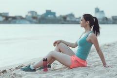 La femme de sports de jeunes se repose après fonctionnement sur la plage Image stock