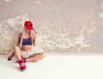 La femme de sports s'assied au mur Photographie stock