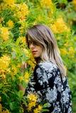 La femme de style pr?s des fleurs jaunes dans a grarden photographie stock libre de droits