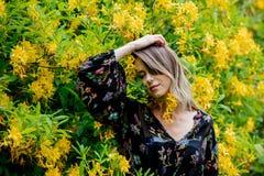 La femme de style pr?s des fleurs jaunes dans a grarden photographie stock