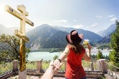 La femme de touristes aux montagnes s'approchent de la croix d'or Image libre de droits