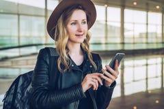La femme de touristes dans le chapeau avec le sac à dos se tient à l'aéroport, tenant le smartphone Email de contrôles de fille,  Images stock