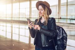 La femme de touristes dans le chapeau, avec le sac à dos se tient à l'aéroport, utilise le smartphone Email de contrôles de fille Photographie stock libre de droits