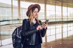 La femme de touristes dans le chapeau, avec le sac à dos se tient à l'aéroport, utilise le smartphone Email de contrôles de fille Photos libres de droits