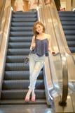 La femme de touristes de voyage et vers le bas un escalator Photographie stock libre de droits
