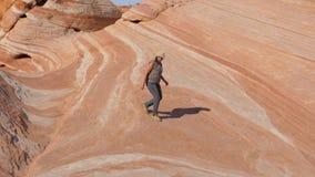 La femme de touristes descend du haut de la colline sur les roches rouges en pierre colorées Photos libres de droits