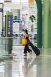 La femme de touristes marche dans l'aéroport Photo stock