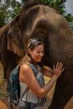 La femme de touristes pose avec l'éléphant adulte images libres de droits
