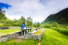 La femme de voyageur prennent le déjeuner sur la nature en montagnes norvégiennes Photo libre de droits