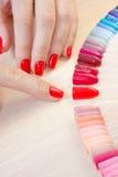La femme de vue supérieure sélectionne le vernis à ongles jaune de gomme laque de couleur Le technicien de clou montre la palette Photo libre de droits