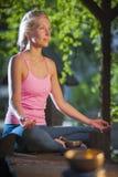 La femme de yoga cross-legged_open des yeux dans le jardin photos stock