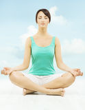 La femme de yoga méditent se reposant dans la pose de lotus au-dessus du ciel Images stock