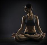 La femme de yoga méditent se reposant dans la pose de lotus Silhoue Photos stock