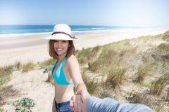 La femme des vacances sur la plage donne la main à son amant pour aller sur le sable de la mer Image libre de droits