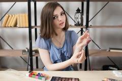 La femme dessine sur la palette en verre avec la peinture théâtrale image libre de droits
