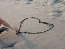 La femme dessine un coeur sur la plage Photos stock