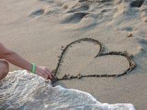 La femme dessine un coeur sur la plage Photo stock