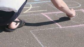 La femme dessine un jeu de marelle sur l'asphalte avec les craies colorées clips vidéos