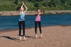 La femme deux faisant les exercices folâtre sur les banques de la rivière dans la ville brancher photographie stock