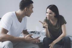 La femme dirige en colère un doigt à l'homme qui s'assied à côté de elle sur le lit et essaye de se justifier photos libres de droits