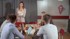 La femme discute avec ses collègues masculins lors de la réunion d'affaires banque de vidéos