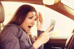 La femme a distrait lire un message sur le téléphone portable, stupéfait, tout en conduisant une voiture image stock