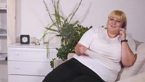 La femme dodue parle du téléphone et sourit banque de vidéos