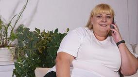 La femme dodue parle du téléphone et sourit photo libre de droits