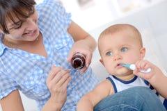 La femme donne à la médecine en difficulté de bébé image stock