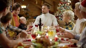La femme donne le cadeau de Noël à son mari pendant le dîner de Noël clips vidéos