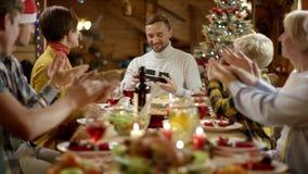 La femme donne le cadeau de Noël pour équiper pendant le dîner de famille banque de vidéos