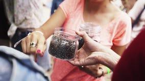 La femme donne le pot en verre complètement de rivets en métal à une autre personne à travailler l'événement banque de vidéos