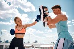 La femme donne un coup de pied l'instructeur pendant la séance d'entraînement dehors photo libre de droits