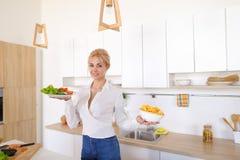 La femme douce tient des plats dans des mains et vérifie la fraîcheur de cuit Photographie stock libre de droits