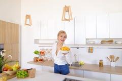 La femme douce tient des plats dans des mains et vérifie la fraîcheur de cuit Images libres de droits