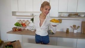 La femme douce tient des plats dans des mains et vérifie la fraîcheur des nourritures cuites, se tenant au milieu de la cuisine m banque de vidéos