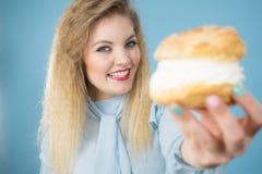 La femme drôle tient le gâteau de souffle crème Photos libres de droits